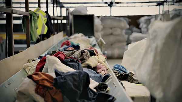 Clothes on a conveyor belt being 'cream graded' at Bristol Textile Recyclers.