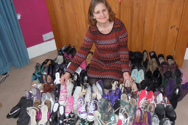Lorinda Trebaczyk with a huge pile of shoes.