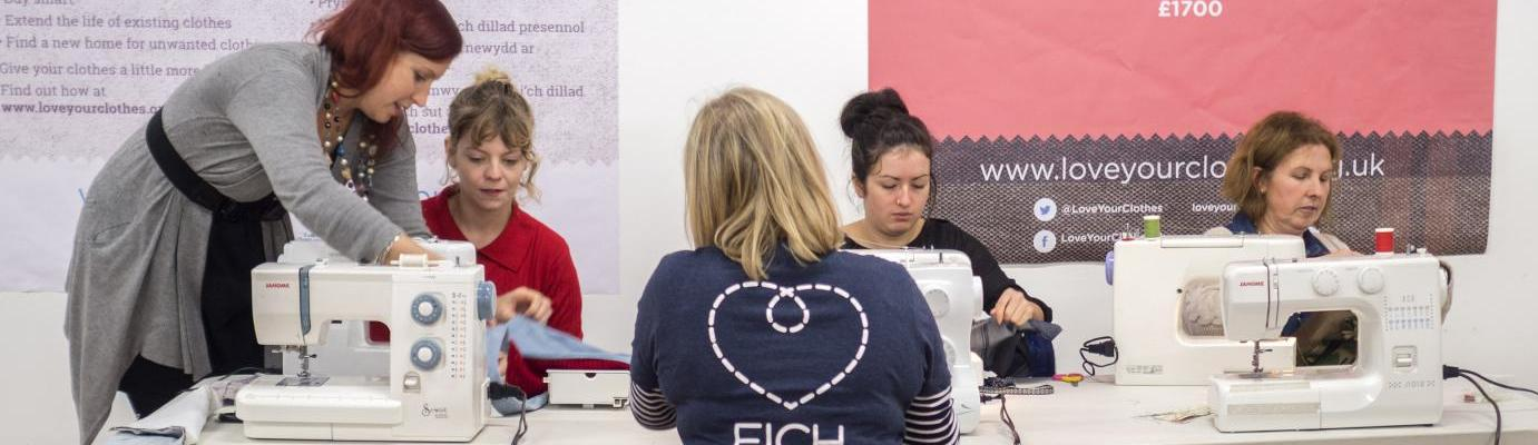Women making tote bags using re-used fabrics and sewing machines at workshop in Cardiff, October 2016.