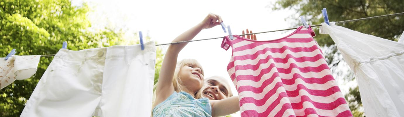 Father and daughter pinning clothes on a washing line.