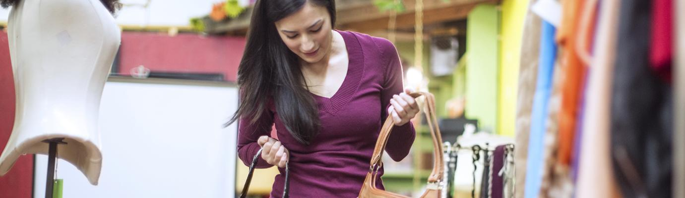 Young woman browsing clothes and handbags in a shop.