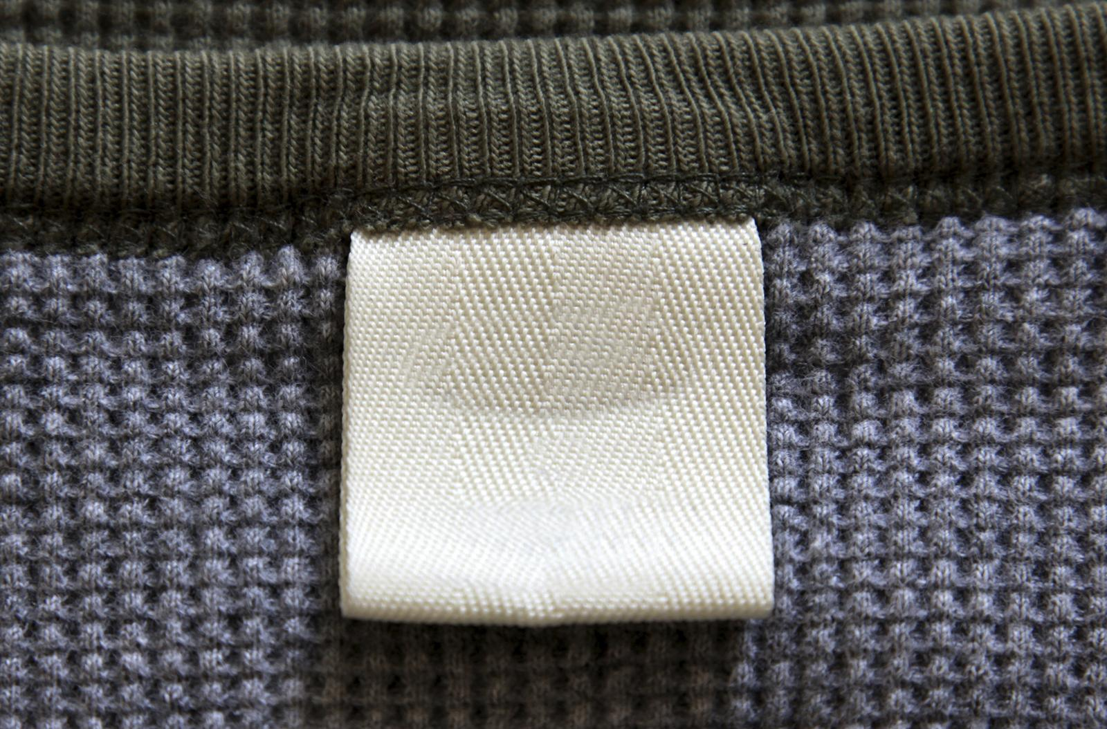The neck of a jumper, showing the clothing label.