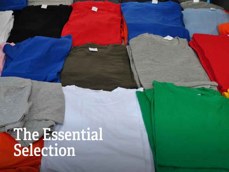 Folded t-shirts in different colours with the headline: The Essential Selection