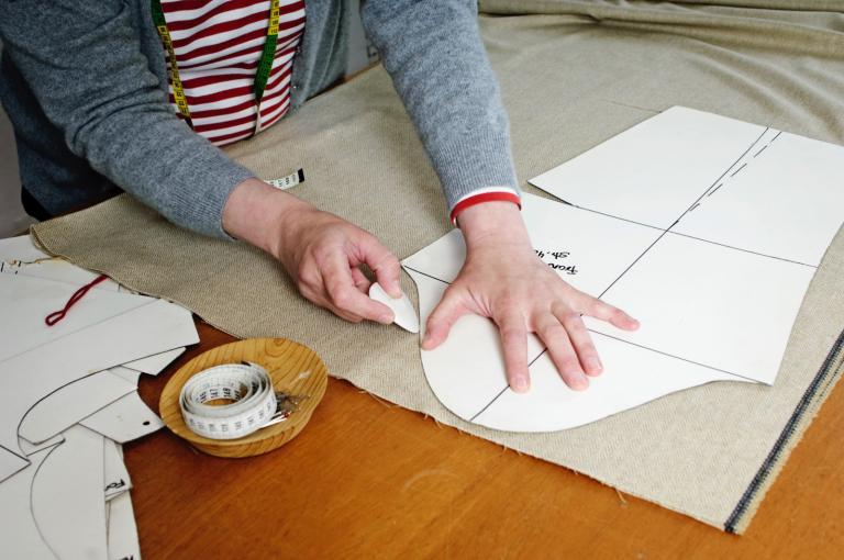 Woman drawing round a paper pattern on a piece of fabric.