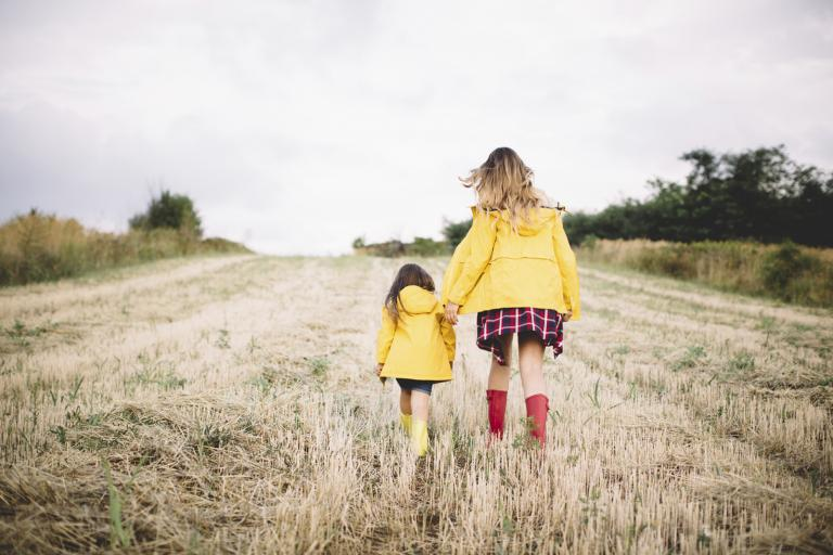 Woman and small girl in a field wearing wellies.