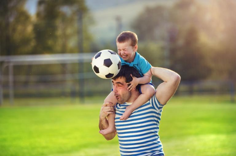 Dad and small boy playing football.