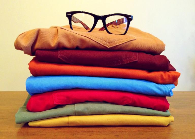 Pile of clothes with a pair of glasses on top.