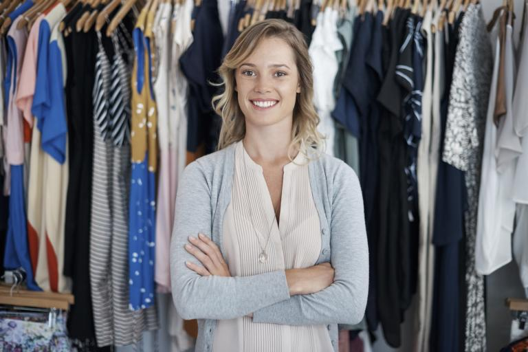 Happy woman in front of a rail of clothes.
