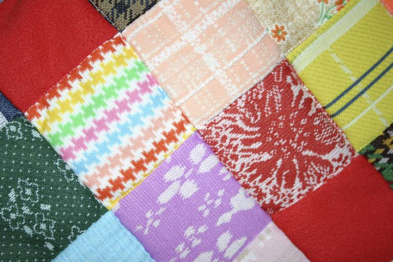 Patchwork made of squares of coloured fabric.