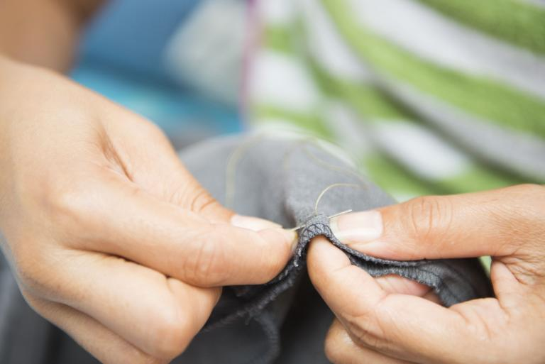 Close-up of hands sewing a piece of fabric.