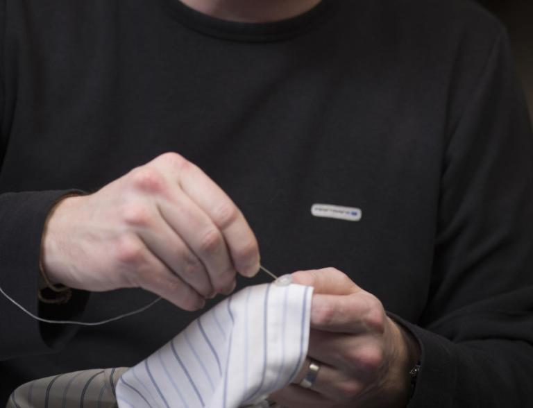 Man sewing on a button.