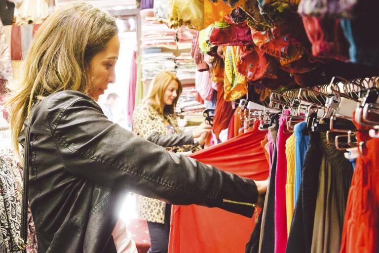 Women browsing racks of clothes.